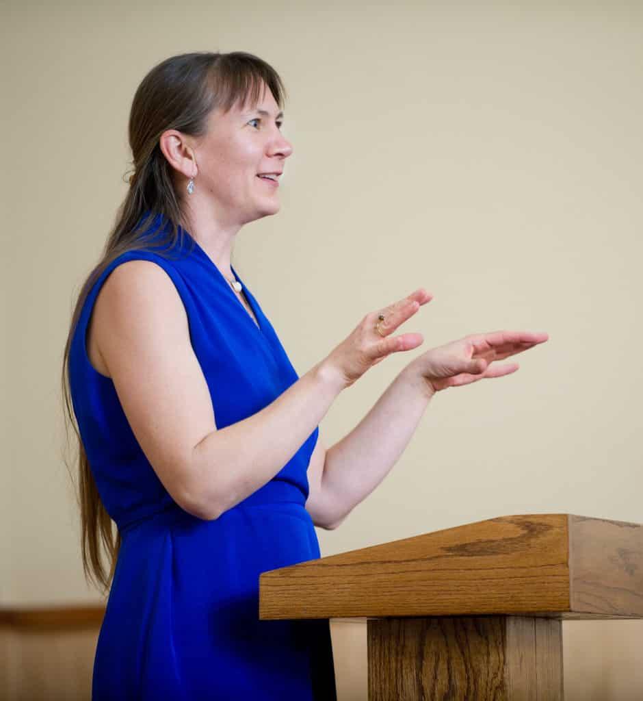 Woman giving a speech at a podium.