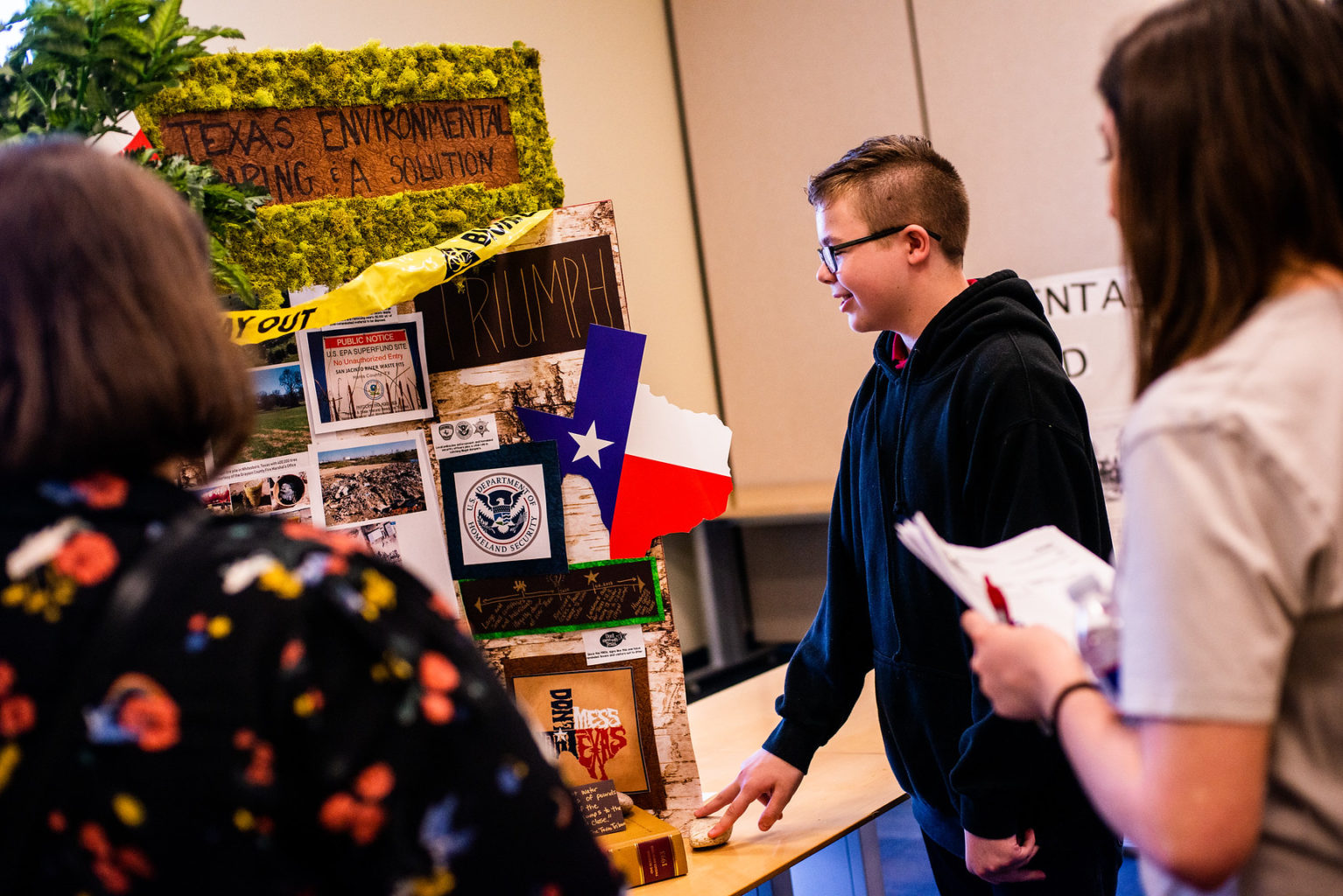 A student present a history project to two teachers.