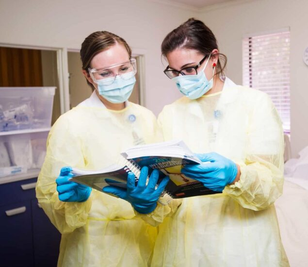 Nurses with personal protective equipment studying a book.