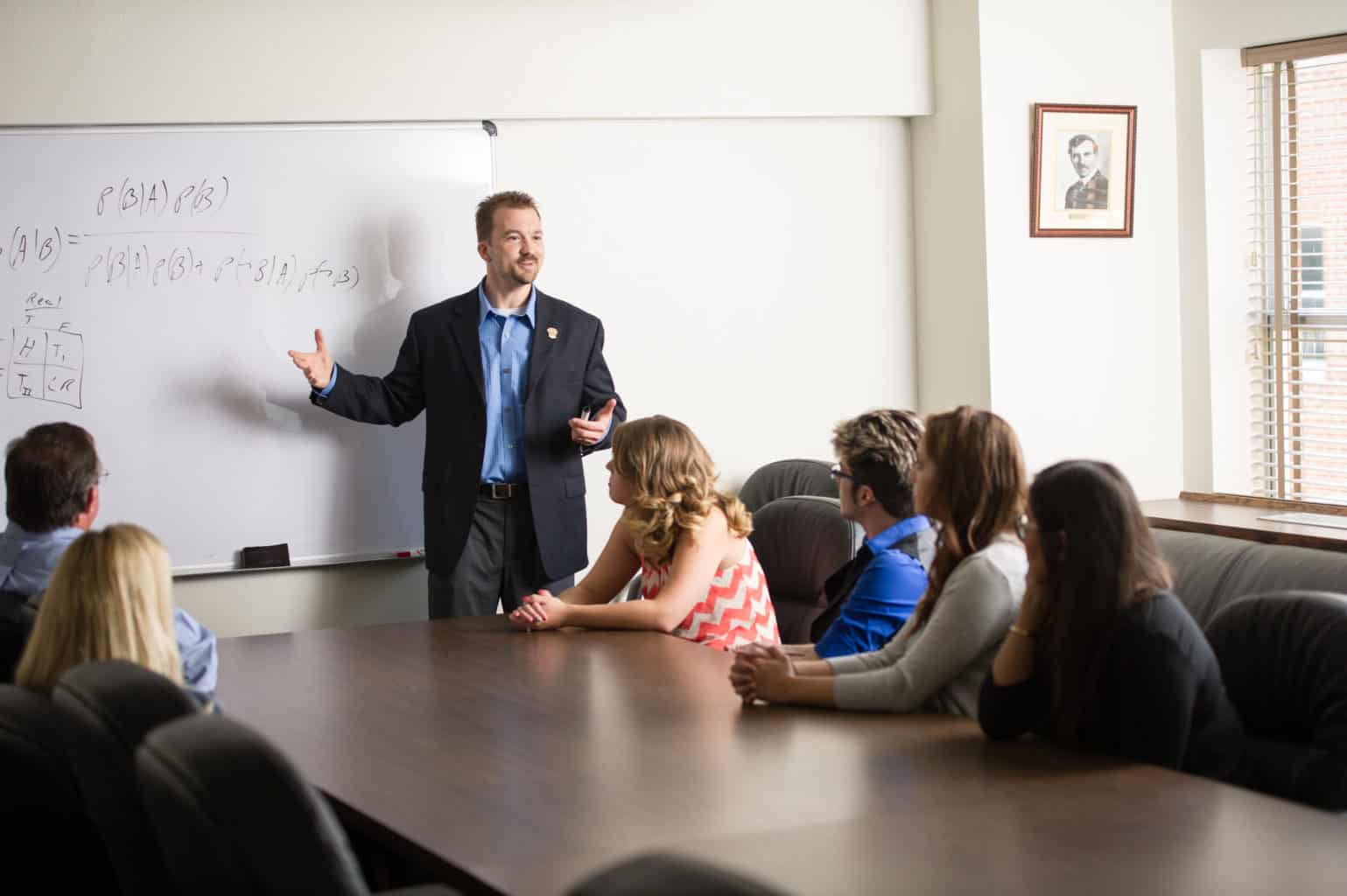 Psychology instructor teaching class around a large boardroom table.