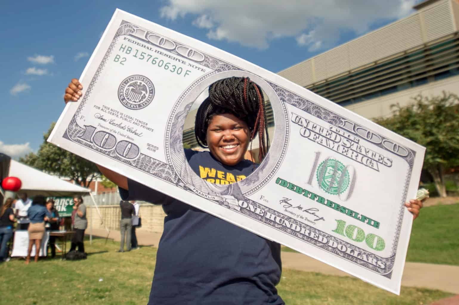 Female with her face inside of a giant one hundred dollar bill.