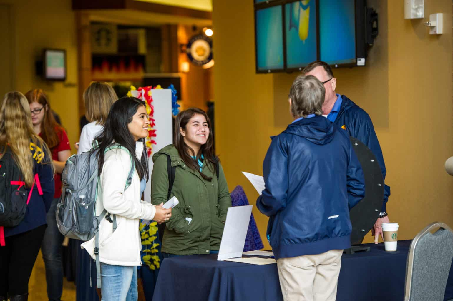 Two students talking with two professors during a student organizations fair on campus.