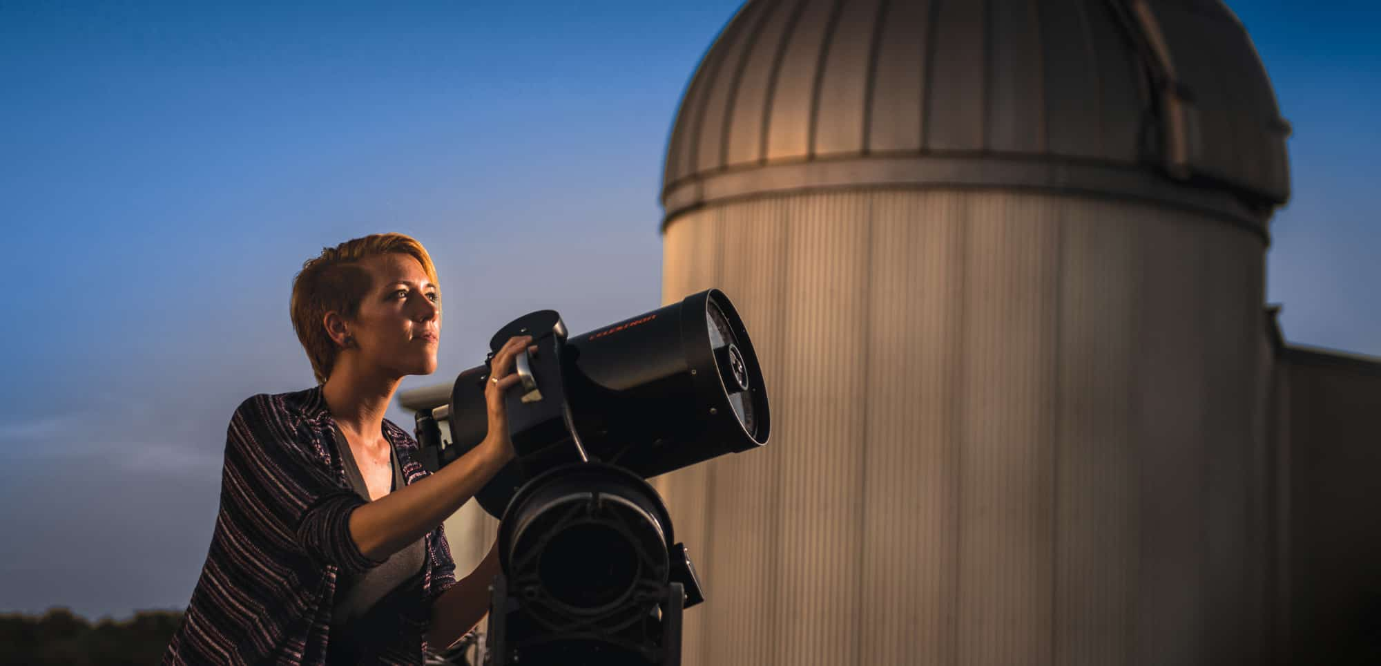 Students viewing stars through a telescope.