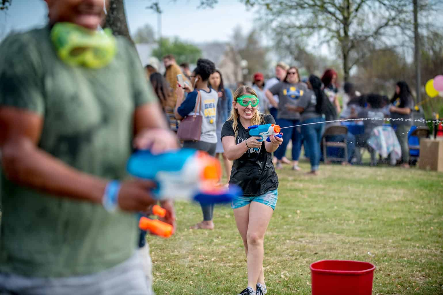 Female shooting water gun while wearing safety goggles.