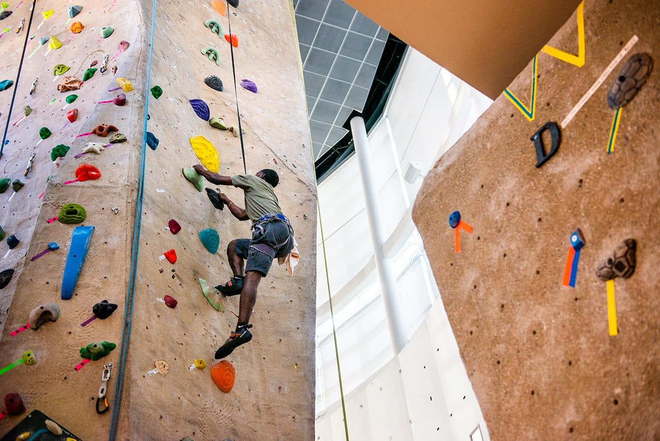 Student climbing rock wall.