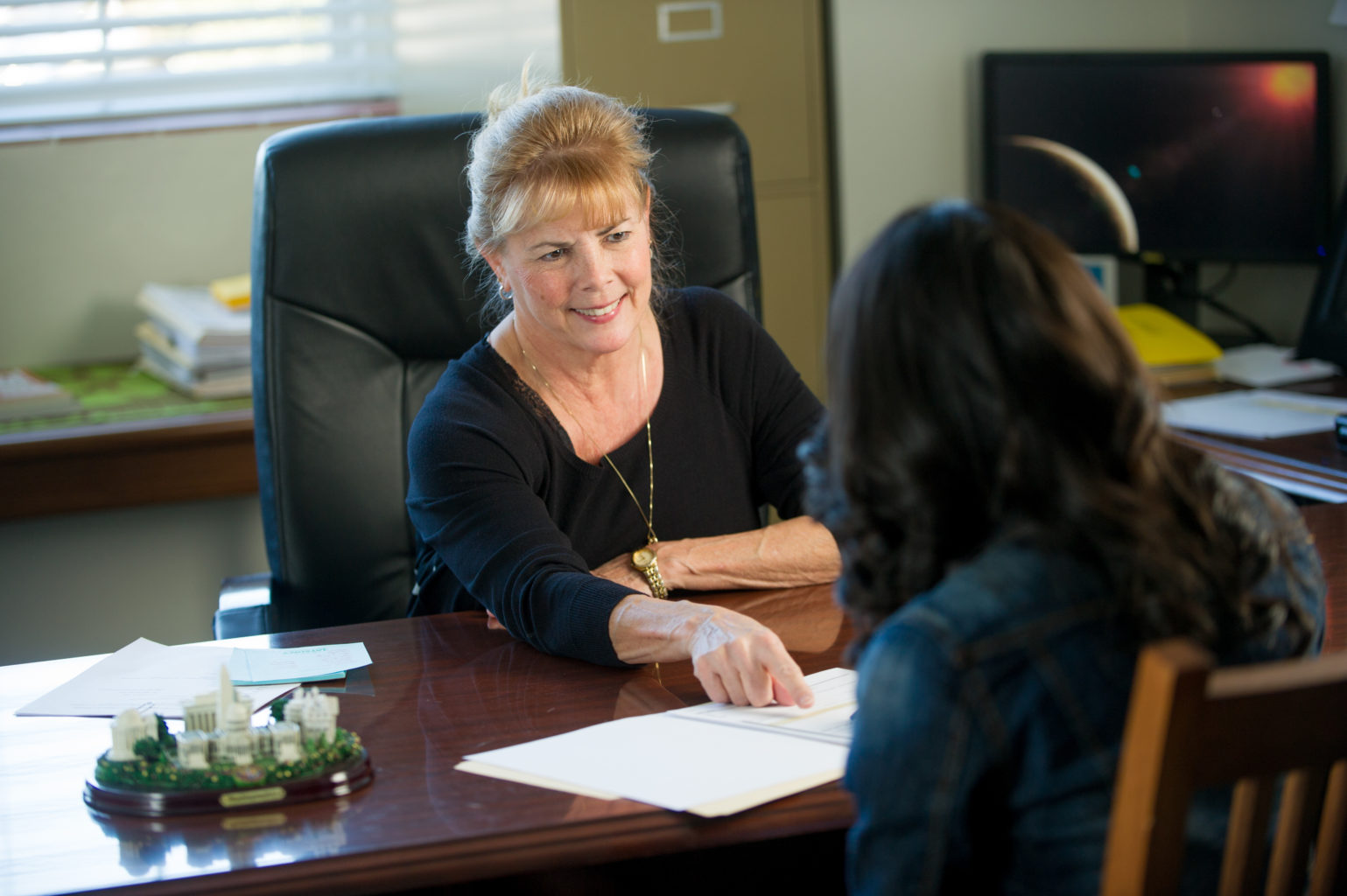 Faculty member smiling with woman at desk while pointing to papers.