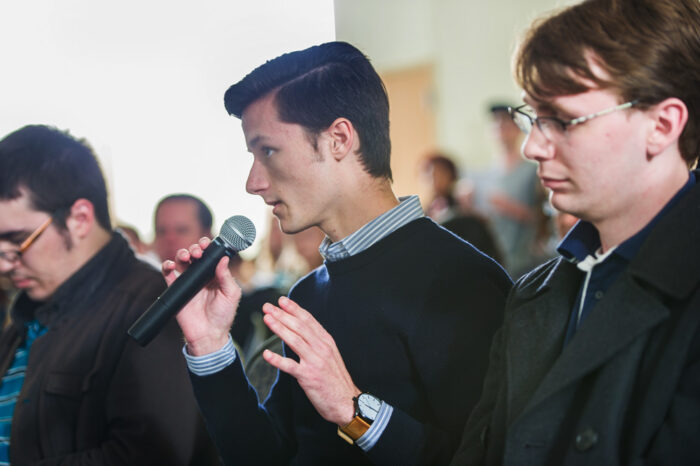 Man speaking into a handheld microphone in a town-hall style meeting.