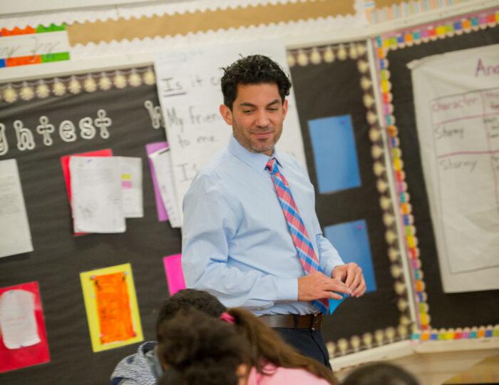 Male teacher in elementary classroom.