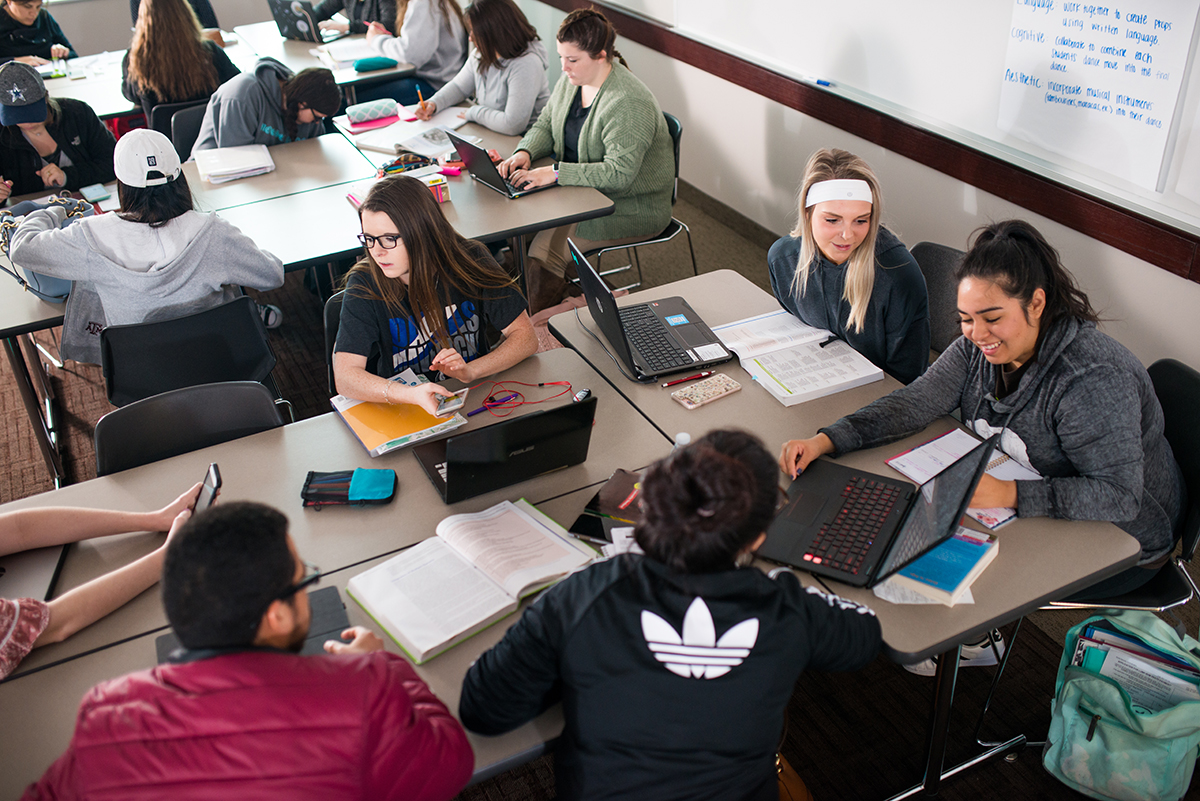 A group of students sitting down in class facing each other, using computers and talking.
