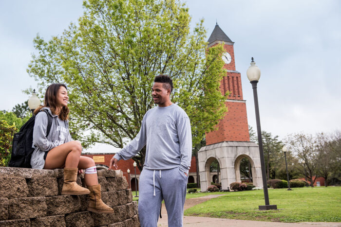Two students talking in an outside space of the A&M-Commerce campus at Navarro College.