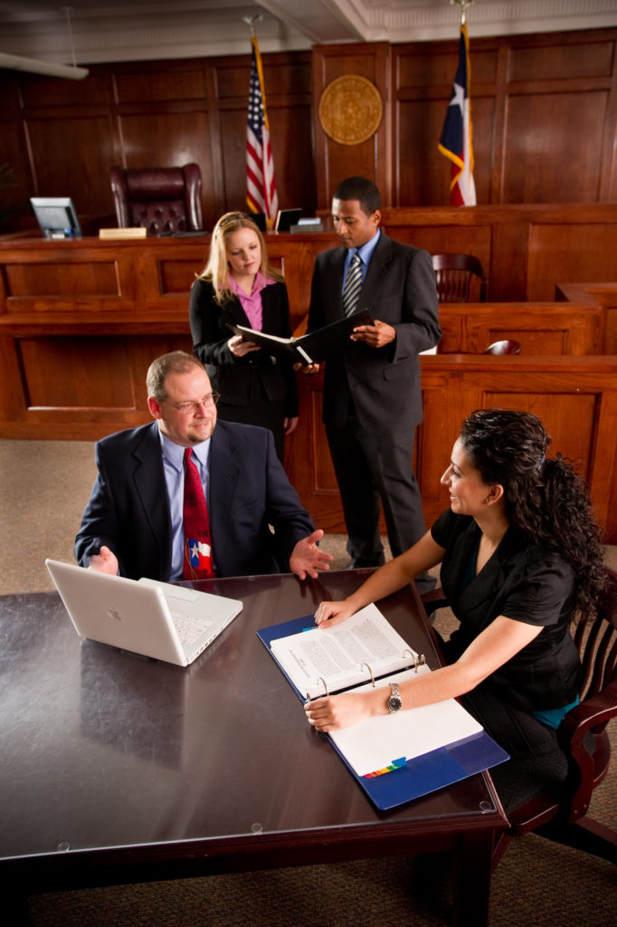 Man and Woman at table in courtroom with another man and woman discussing a case in the background.