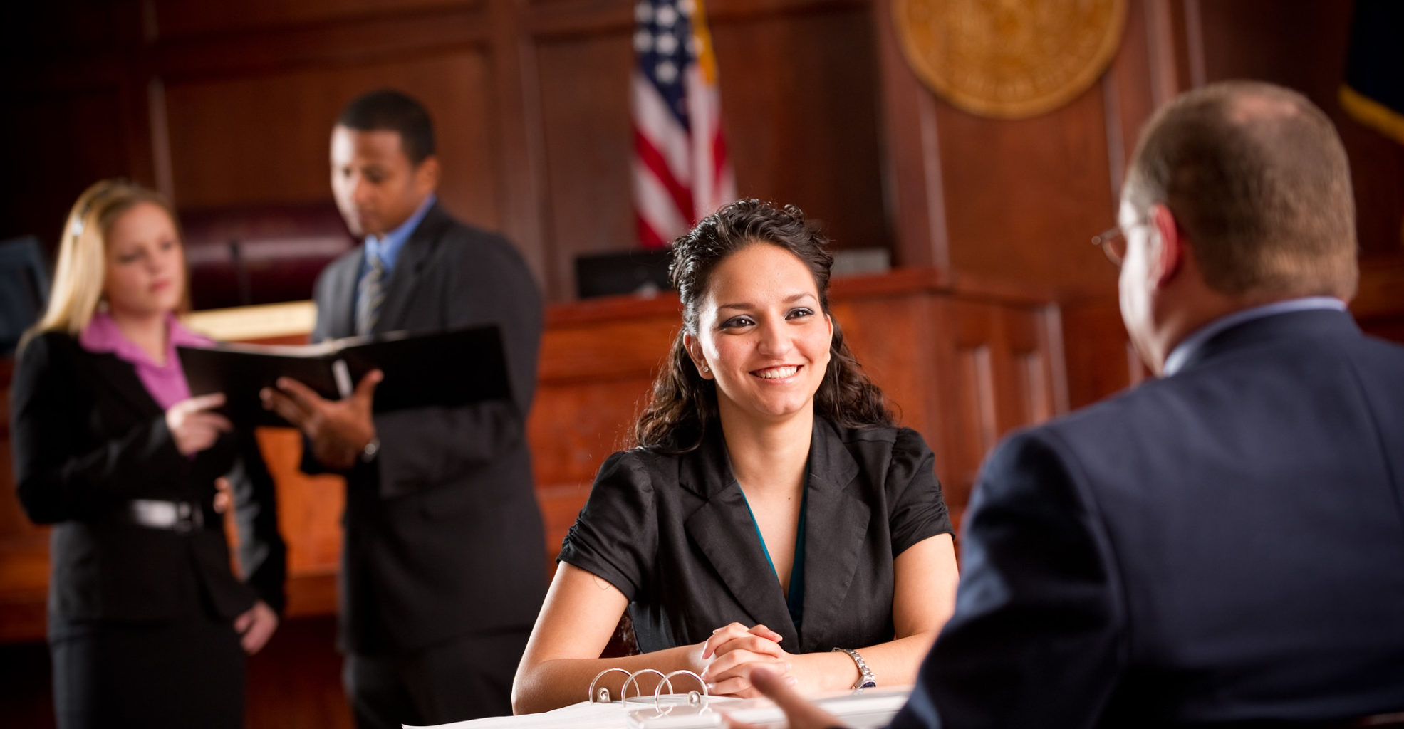 Woman approaching judges desk with individual discussing a case in the background.