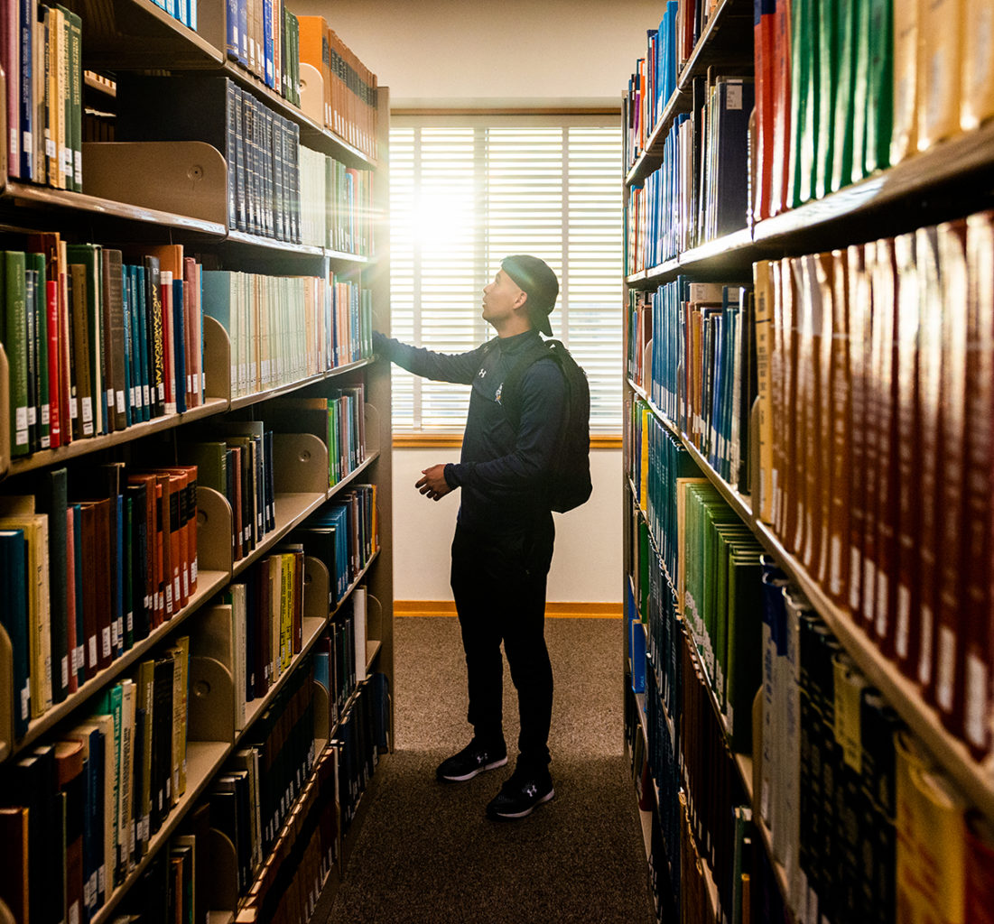 Male student looking for a book in the library.