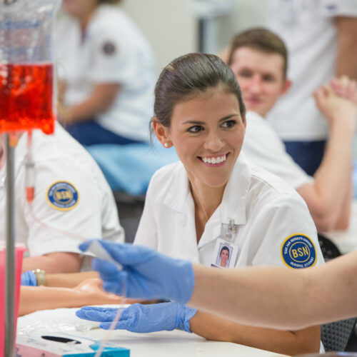 Nursing student smiling while learning.