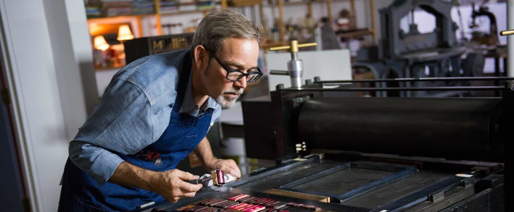Man working on letter press for art project.