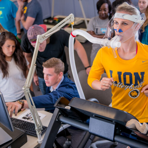 Professor and students observing a health and human performance test including a female athlete running on treadmill.