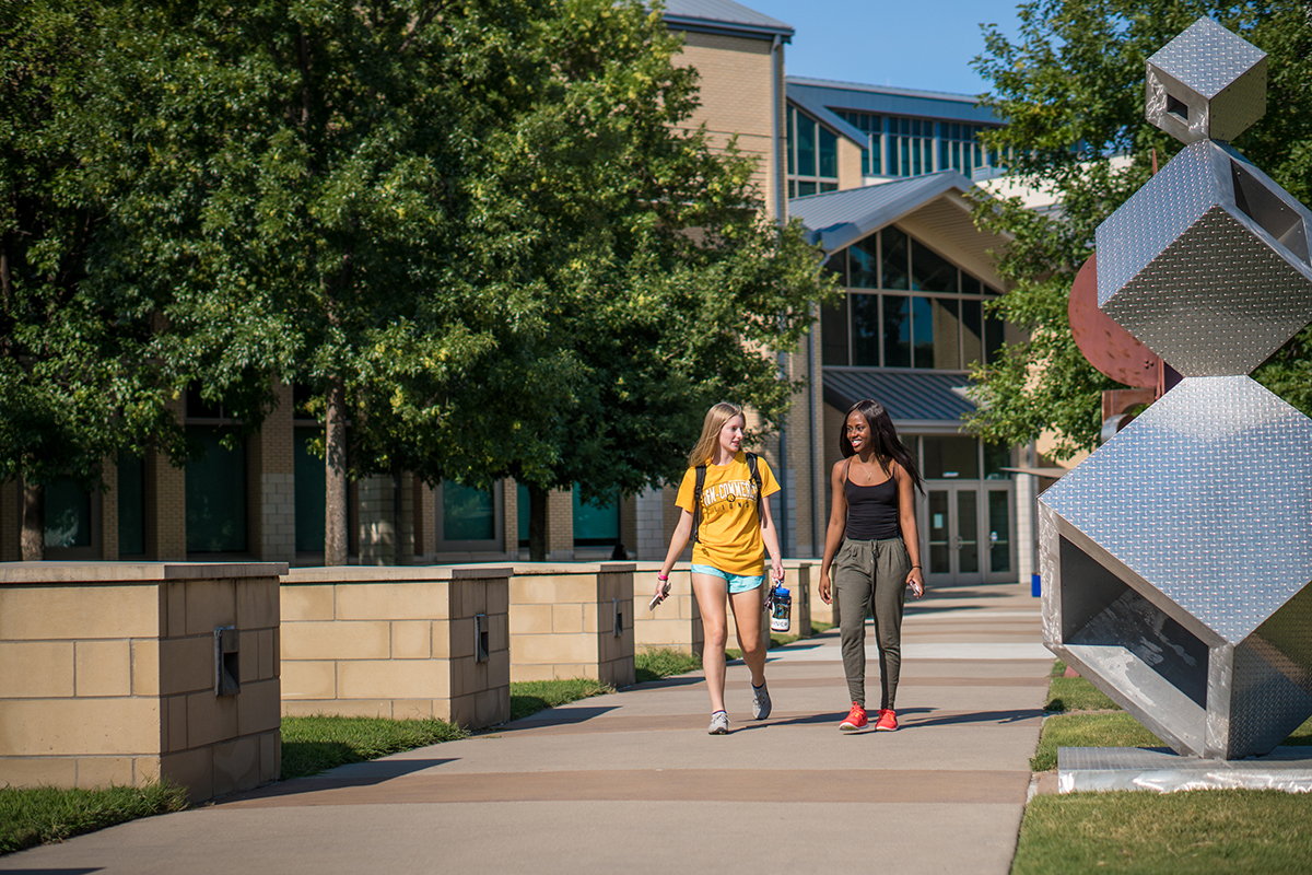Two females one dressed in gold and blue, the other in black and green are walking down the sidewalk on the Collin College's campus talking to each other.