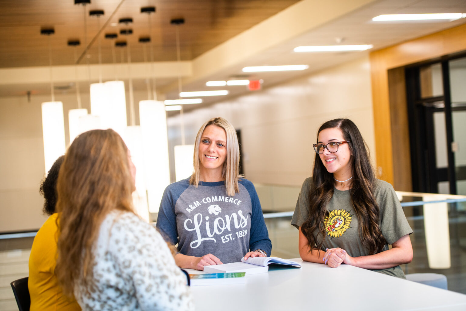 A group of 4 females talking with a book open on a table.