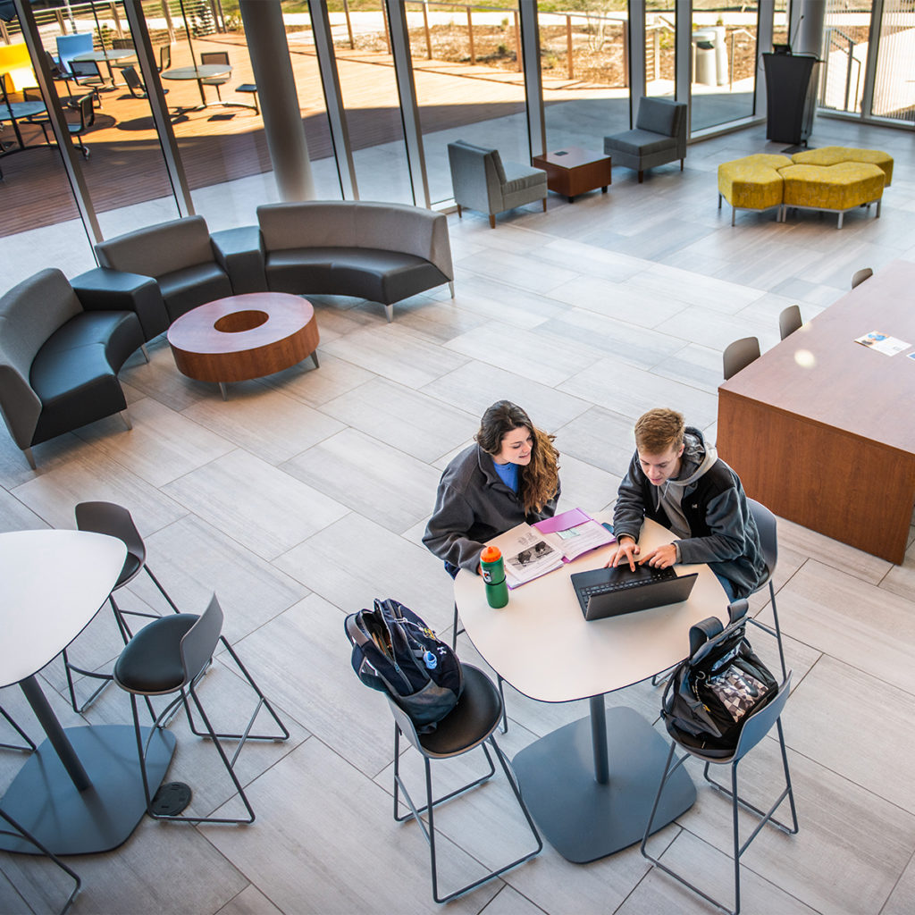 Two student sitting down at a table looking at a laptop in the common area of the nursing and health sciences building.