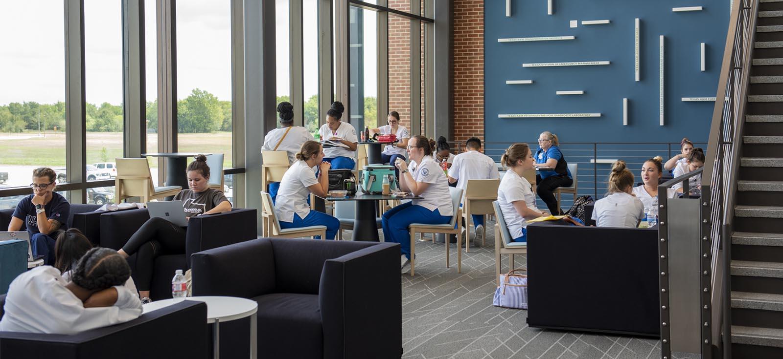 different groups of students eating, reading and talking in a student lounge at the Rellis location.