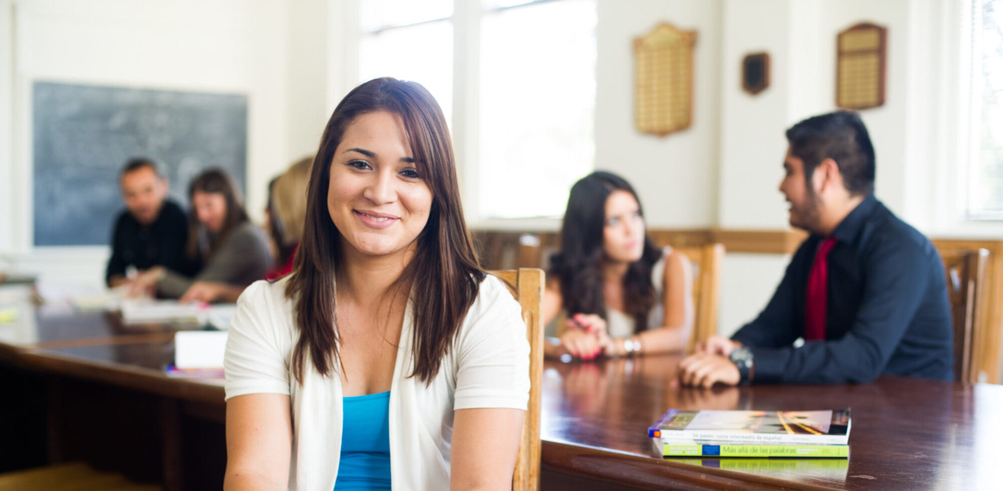 Female student smiling with college classmates at table behind her.