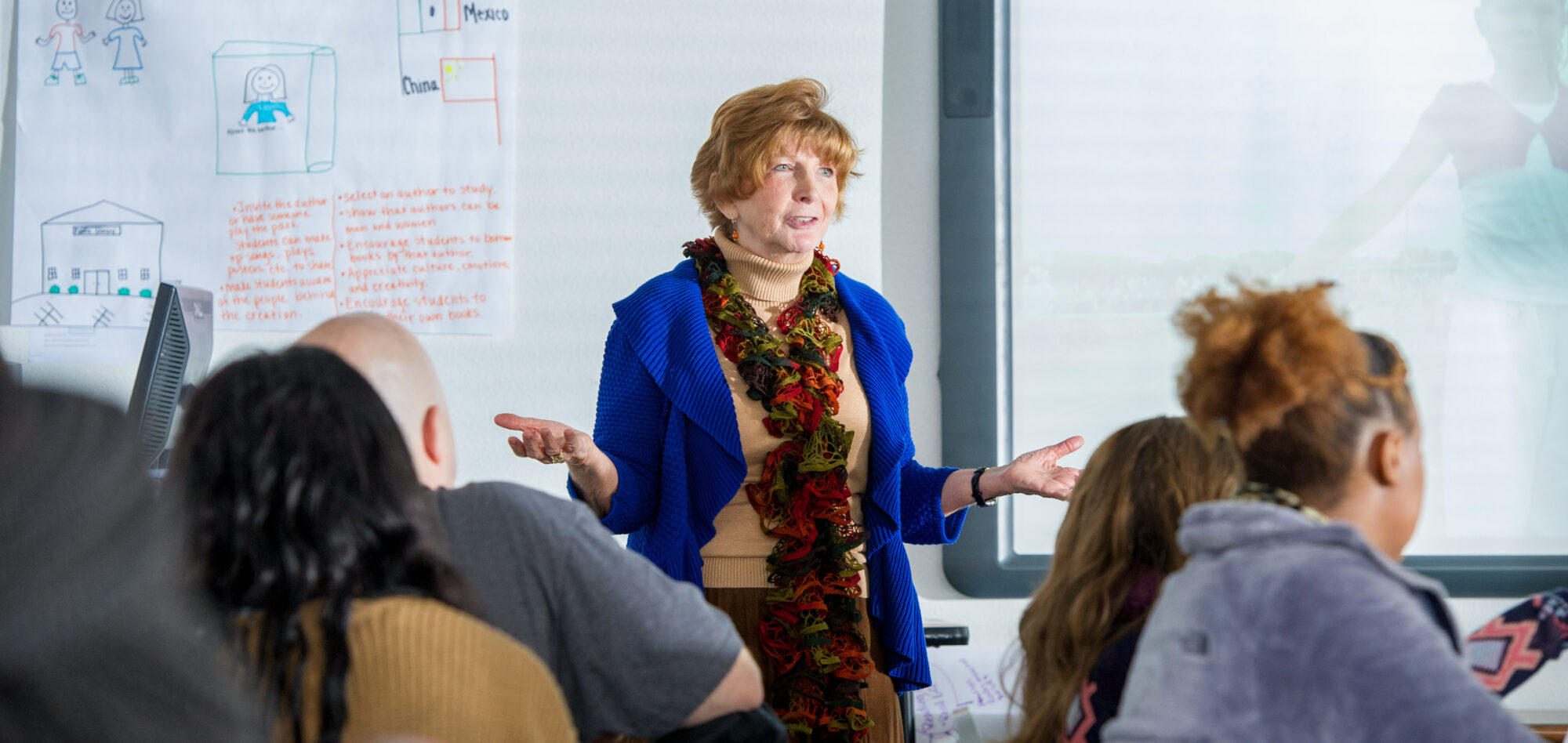 Woman teaching classroom full of college students