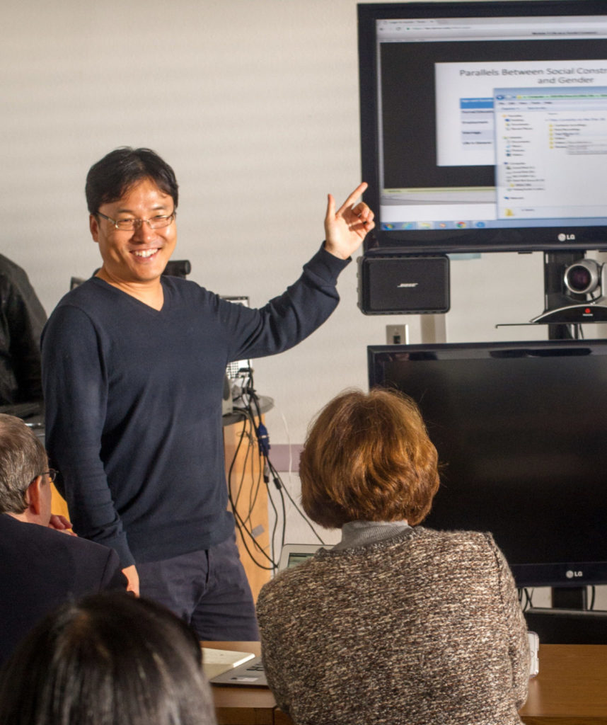 Man pointing to large computer screen while teaching class.