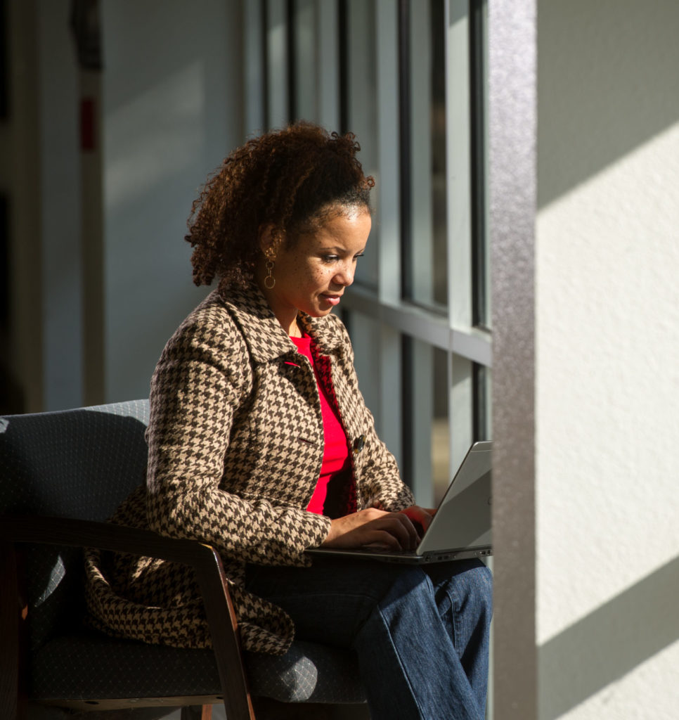Woman working on laptop seated facing windows.