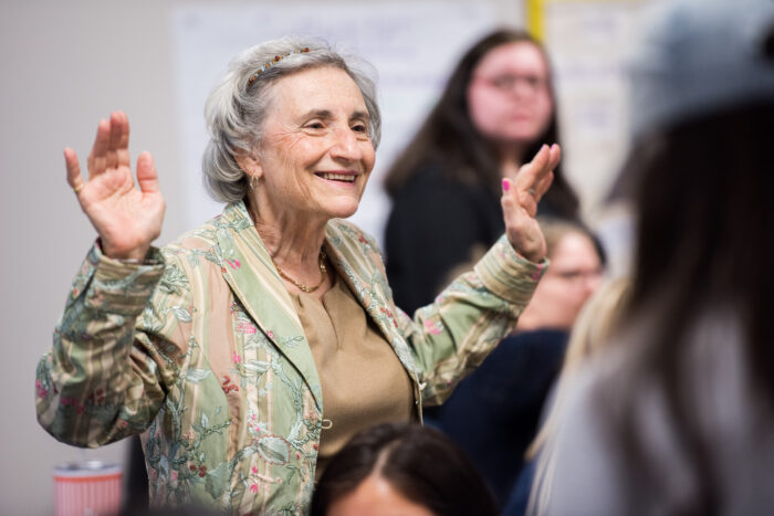 Older female educator standing in classroom with raised hands and smiling