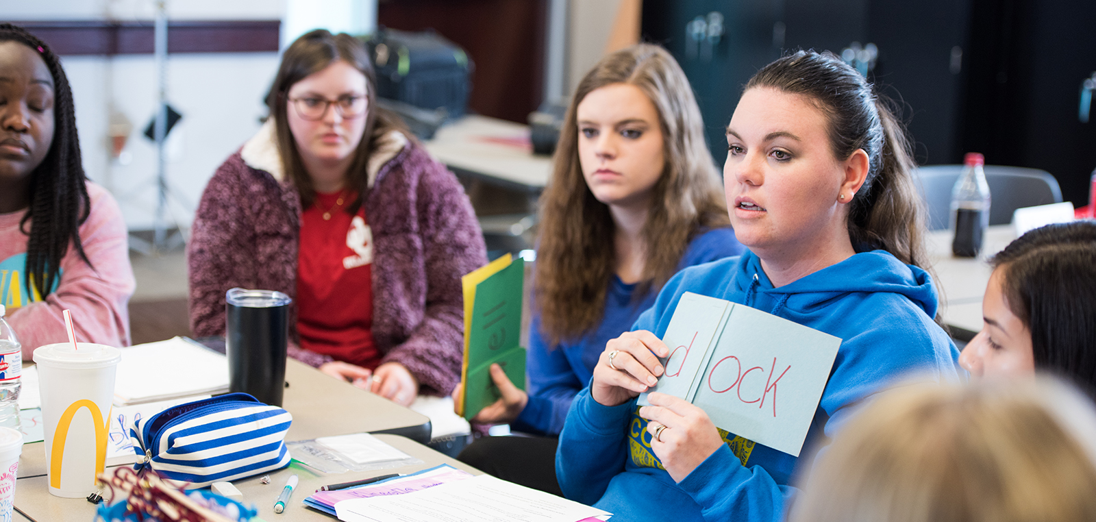 A student holding a blue piece of paper with a word wrote on it, in class.