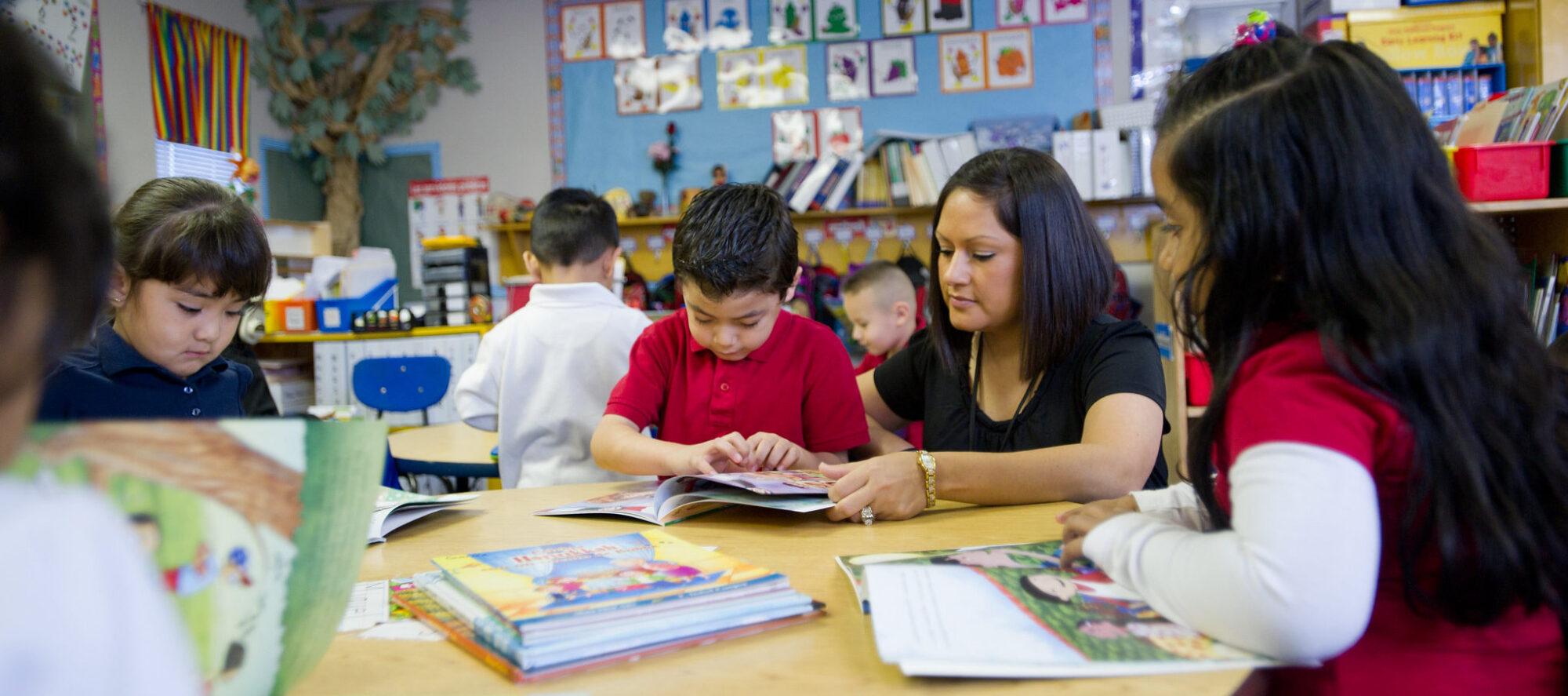 hispanic female teacher help young hispanic boy in classroom.
