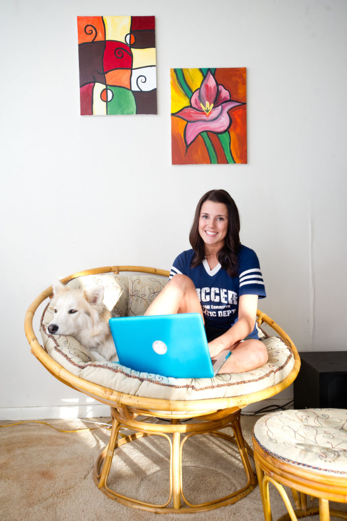 Female student on chair with dog and laptop working on online course.