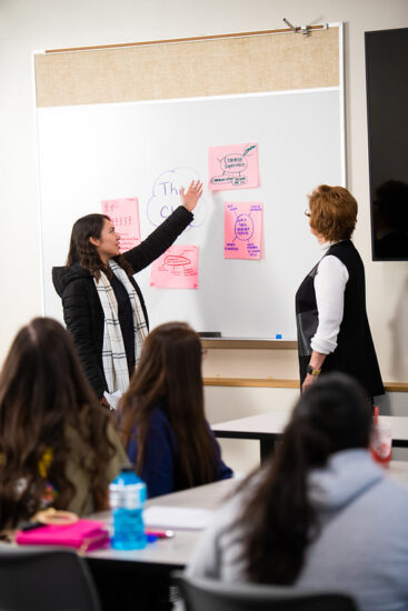 Female student presenting in front of class at a white board with female teach watching.
