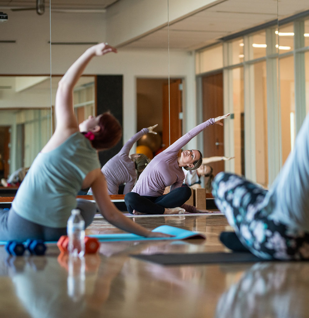 Students during a yoga session inside the nursing and health sciences building.