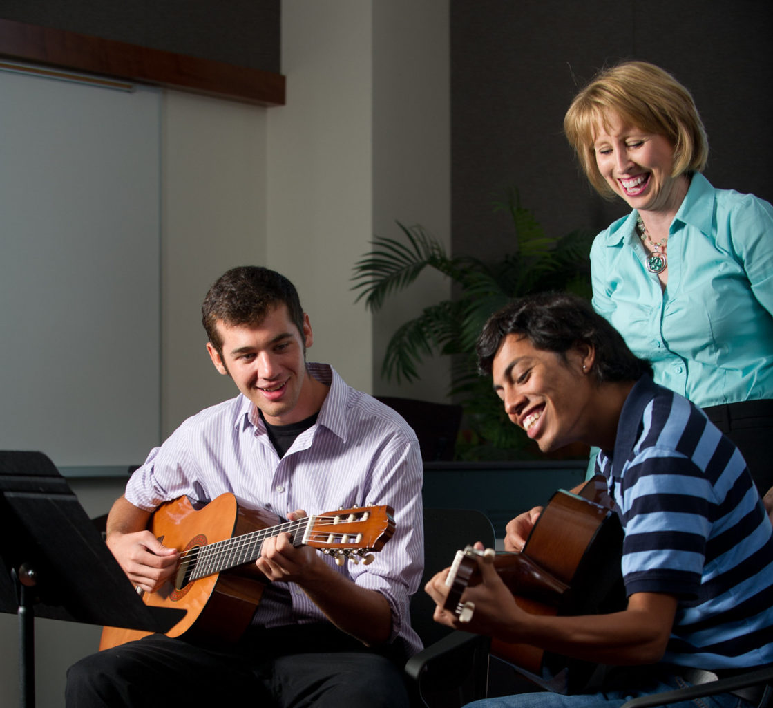 Two male students playing guitar with female instructor in the background.