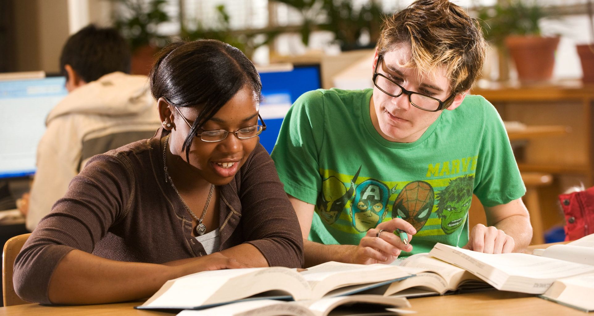 female and male student stying books at table.