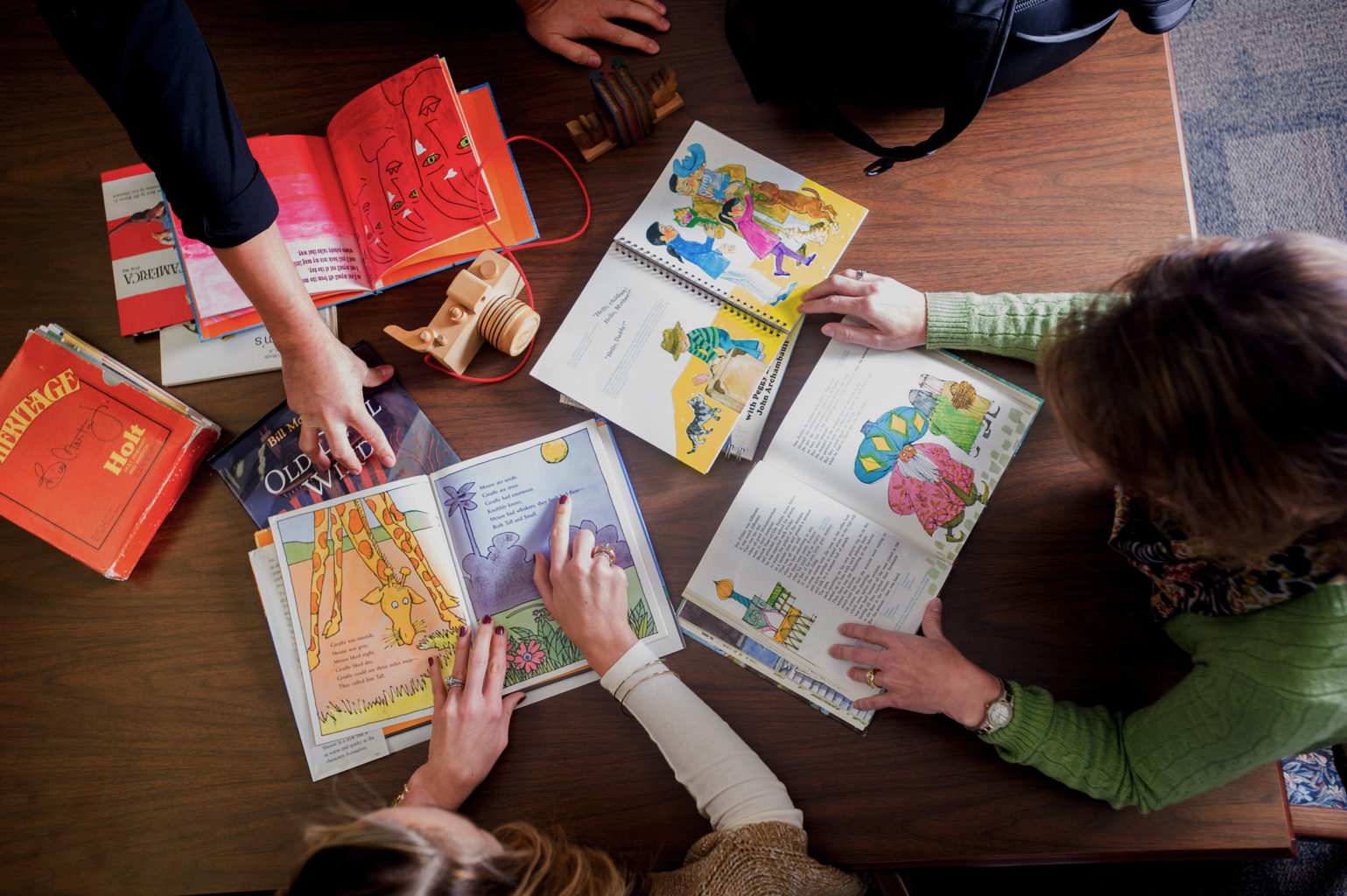 On top view of three people looking over children's book places on a desk.