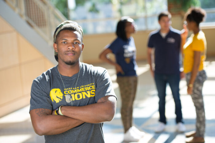 Student wearing a TAMUC shirt on campus.