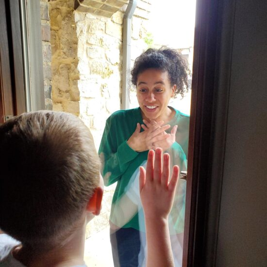 A teacher interacting with a student through the glass of their front door during pandamic.