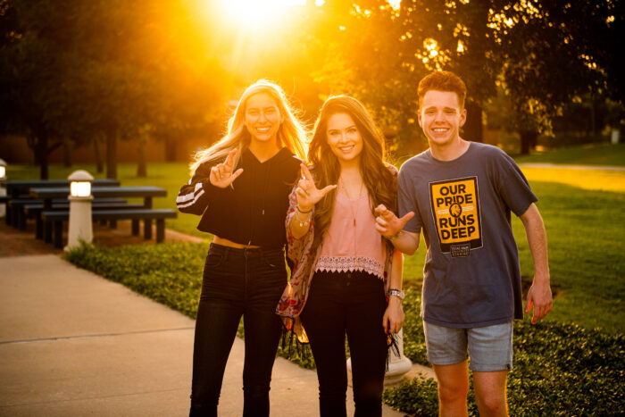 three students making the TAMUC sign while taking a picture on campus with the sunset behind them.