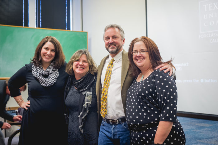 Group of professors standing in a classroom.