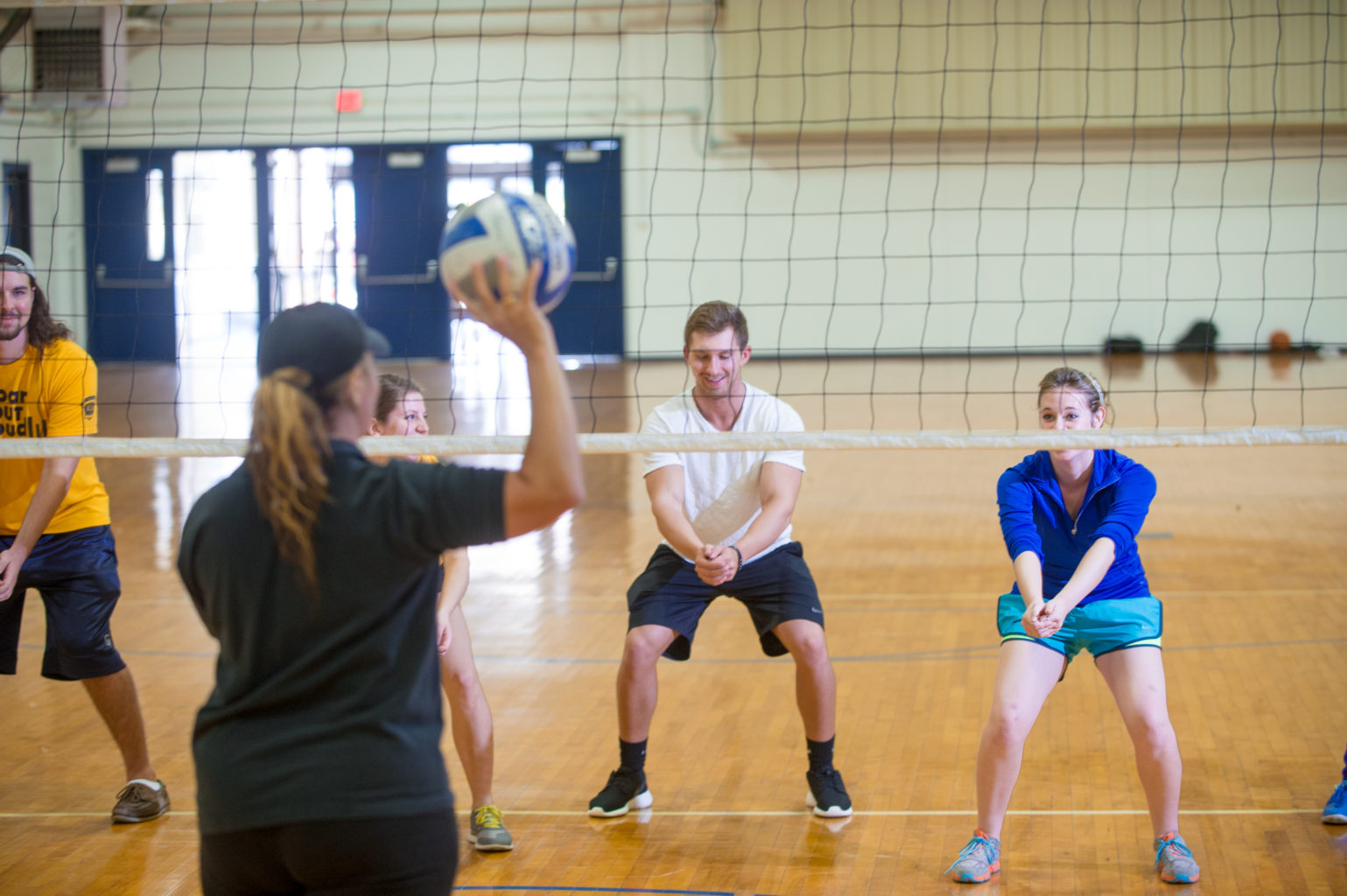 Student learning volleyball inside the Gym in the Commerce campus.
