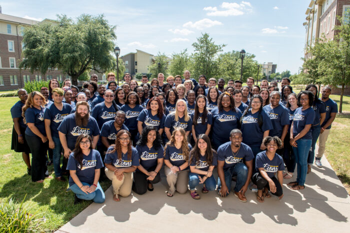A group photo of TAMUC students wearing the same TAMUC blue shirt.