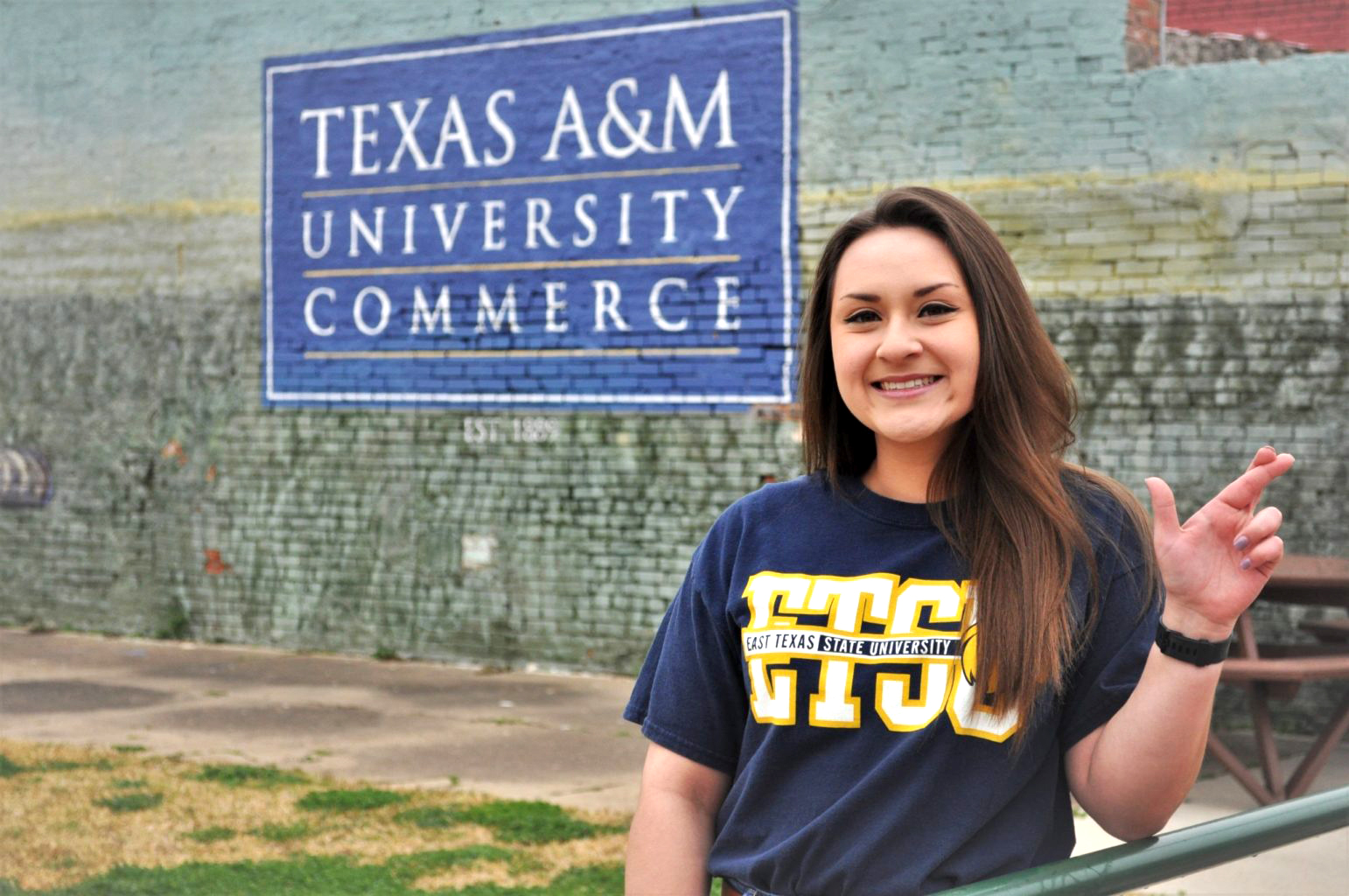 Picture of Heather Rodriguez making the lion sign with behind a mural of Texas A&M University Commerce.