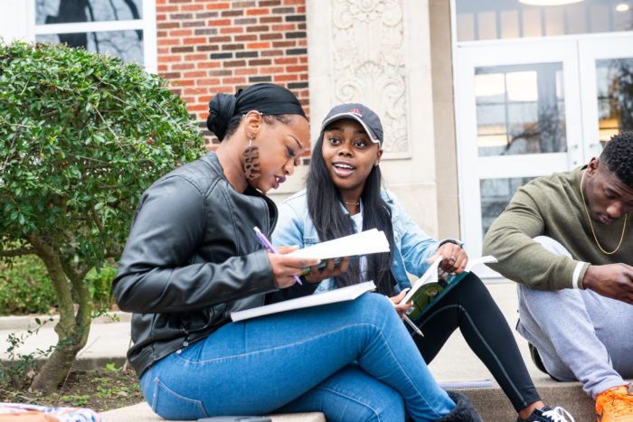 Students studying on the steps outside.