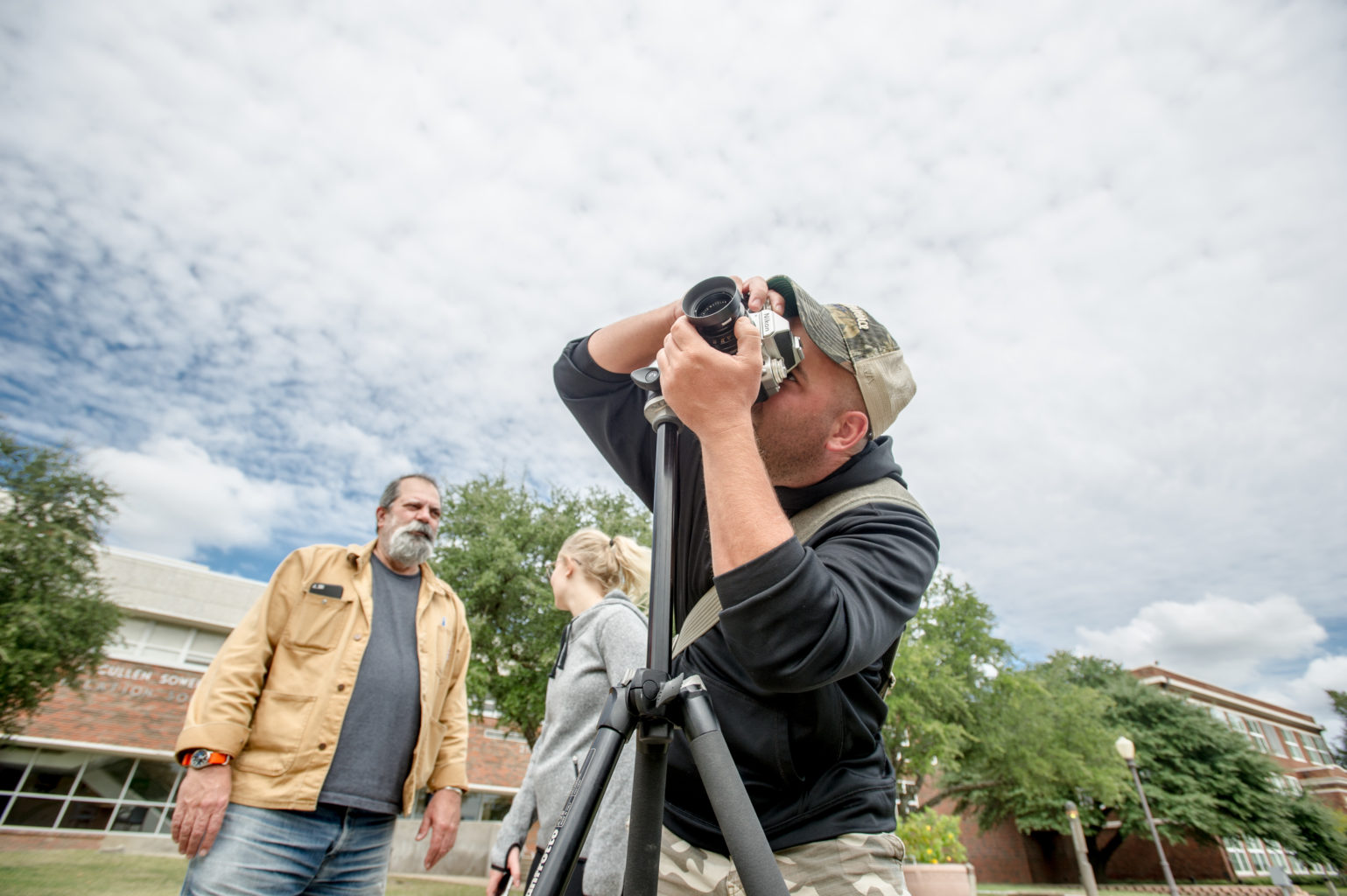 man shooting photos with an older man and woman in the background.