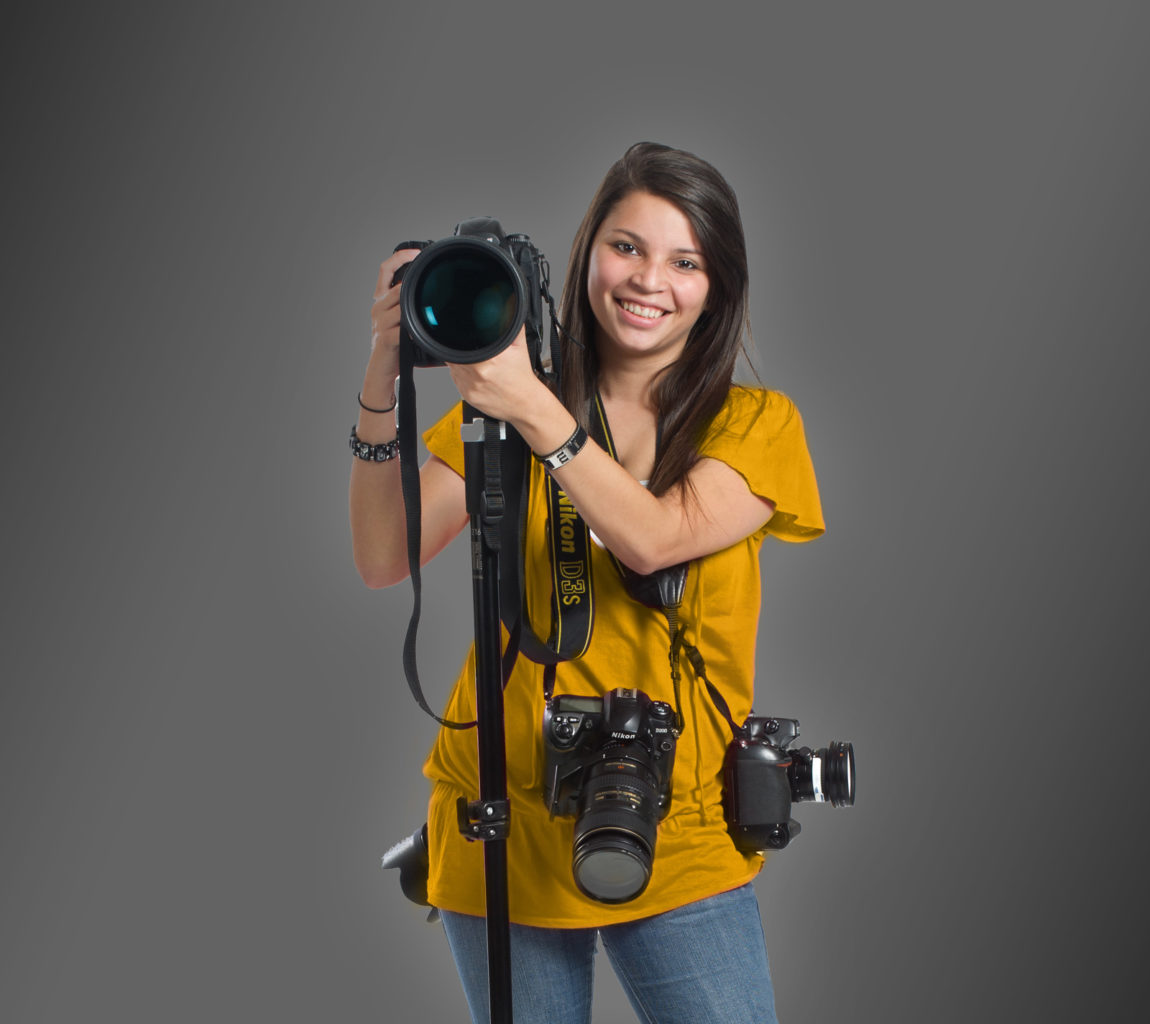 Young woman holding multiple cameras.