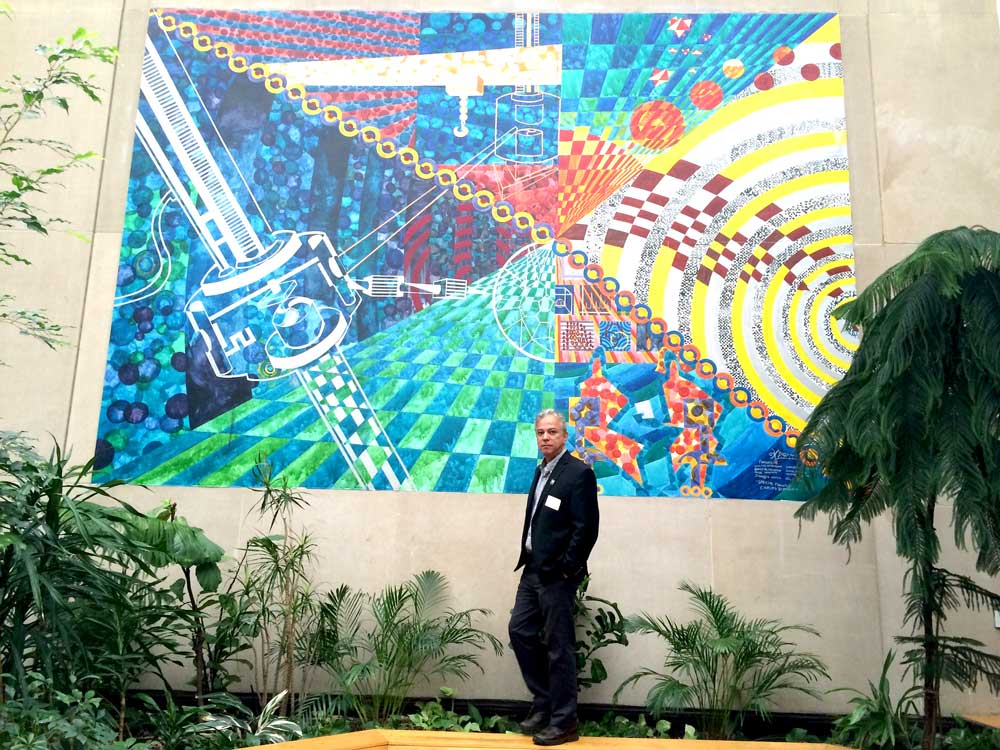 Dr.-Bertulani-standing-in-front-of-the-mural-Coupling-of-the-Cyclrotron-in-the-Atrium-of-the-FRIB-facility-at-Michigan-State-University-which-was-painted-by-his-son-noted-artists-Henrique-Bertulani.