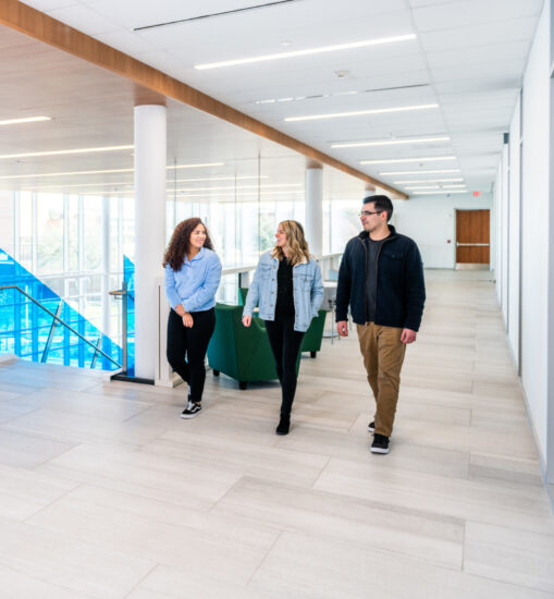 Three student walking inside the A&M-Commerce Nursing Health Sciences building.