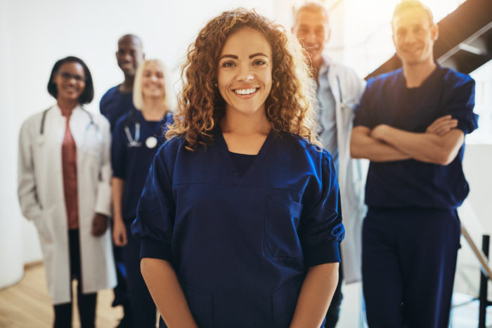 Smiling female doctor standing with medical colleagues in a hospital.
